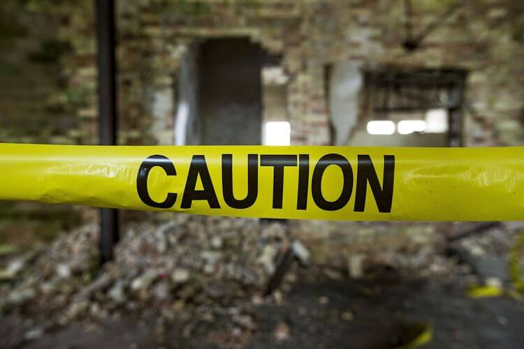 caution police tape around crumbling building