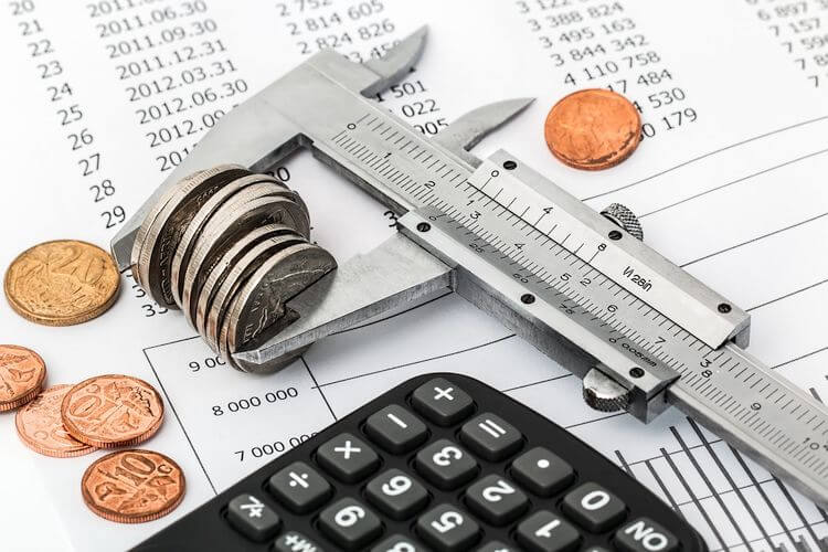 calipers holding coins next to calculator