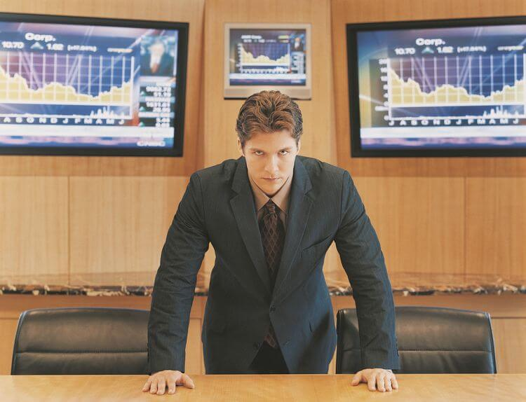man in suit leaning forward over a desk