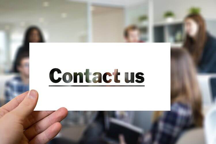 person holding card with the words contact us
