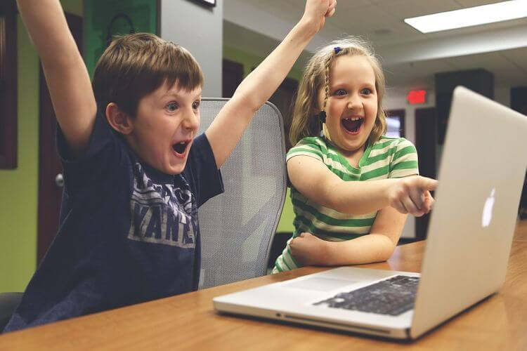 2 children smiling in front of a laptop