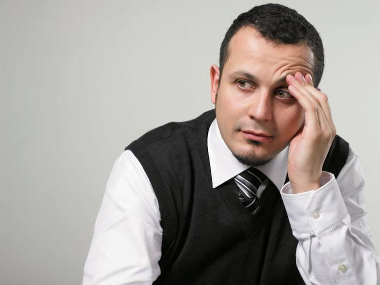 man thinking holding forehead