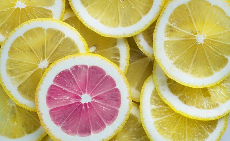 one pink slice among many yellow lemon slices