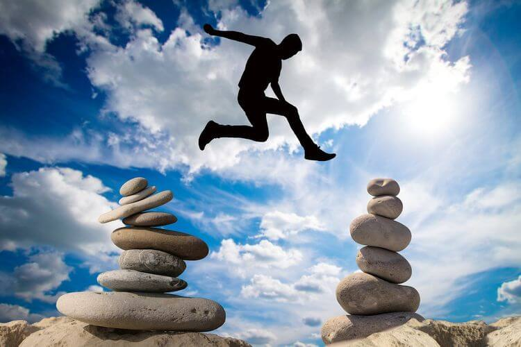 man jumping between tall balanced rock piles