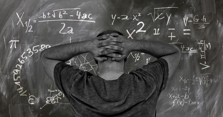 man calculating on chalkboard