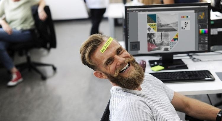 smiling employee by computer